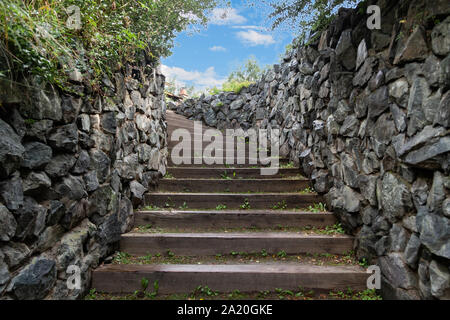 A long high staircase with wooden steps extending upward going to the blue sky surrounded by stone walls in summer. Business and career growth, the pa - Stock Photo