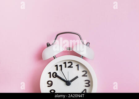 Retro analog alarm clock on pastel pink background - Stock Photo