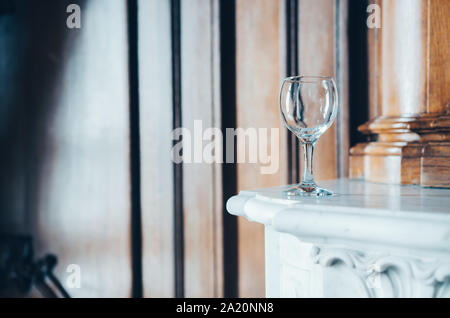 Empty wineglass on the mantelpiece in a beautiful interior - Stock Photo