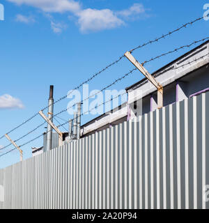 Barbed wire stretched in three threads over a metal fence of gray profiled sheet, industrial structure and chimneys behind the fence - Stock Photo