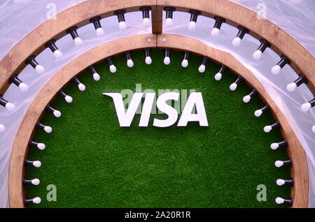KHARKOV, UKRAINE - MAY 12, 2018: VISA logo on green grass in photozone with many white lightlamp bulbs ad wooden plank - Stock Photo