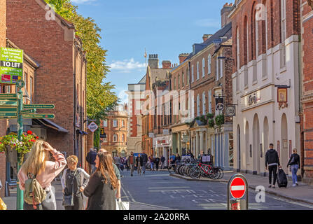 A street scene at the junction of Lendal and Museum Street in York. Shoppers mingle under a signpost and historic buildings line the street. - Stock Photo