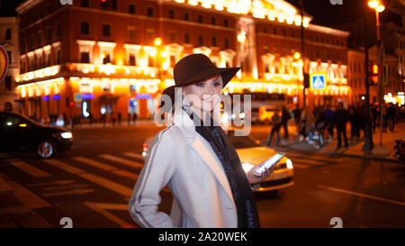Stylish young woman in an elegant beige coat uses a smartphone standing by the road, on the street of the city at night. Beautiful blonde talking on t - Stock Photo