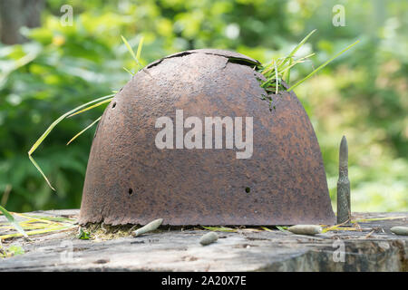 Leningrad Region, Russia - August 6, 2019 - a rusty Finnish battle helmet from World War II period excavated in Karelia, north of Saint Petersburg - Stock Photo