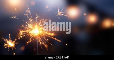 Glittering burning sparkler against blurred bokeh light background