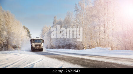 truck on winter road covered with snow - Stock Photo