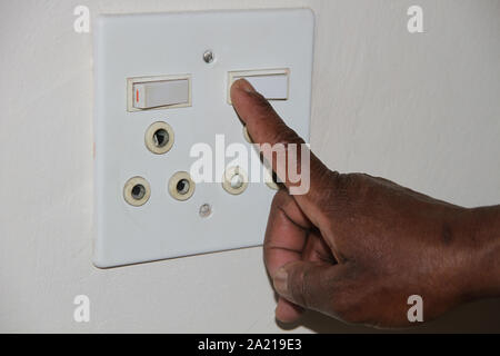 Close-up of hand switching off a white double power socket, South Africa. - Stock Photo