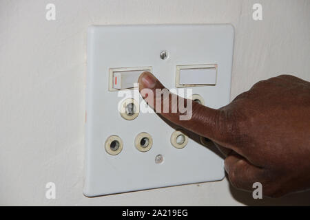 Close-up of hand switching on a white double power socket, South Africa. - Stock Photo