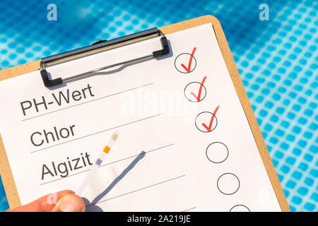 Checking the water quality of a pool with the help of a test strip with the words PH value, chlorine and algaecide in German language - Stock Photo