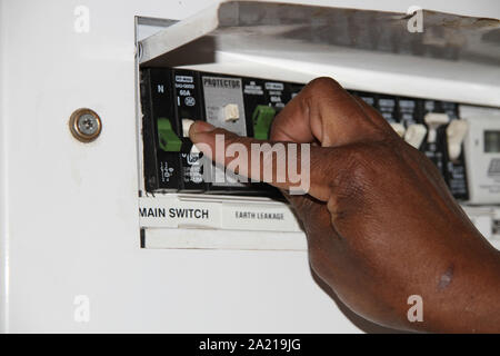 Close-up of hand switching off the main switch on a switchboard, South Africa. - Stock Photo