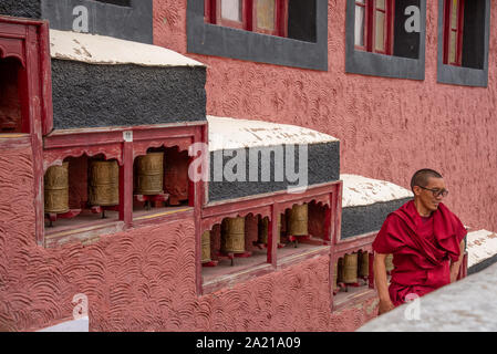 monk and praying wheel at Thiksey monastery in Ladakh, India - Stock Photo