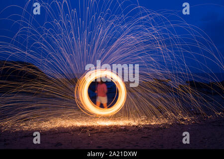 A woman doing circular spinning light painting using steel wool at night on the beach. - Stock Photo