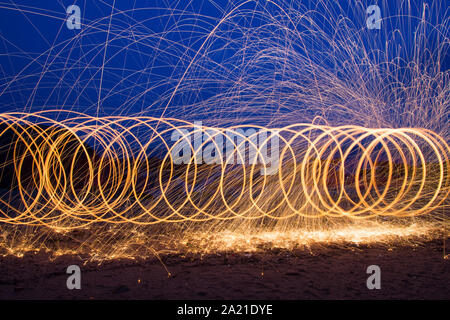 Circular light painting using steel wool at night on the beach. - Stock Photo