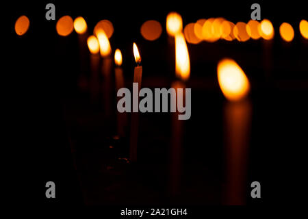 Burning candles with shallow depth of field candlelight background image for diwali festive decoration or church celebration at night with copy space. - Stock Photo