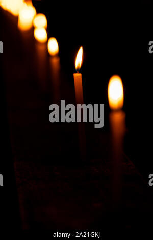 Beautiful candles burning in a row or line pattern at a temple or church during Diwali celebration or ceremony at night. Background stock photo of fes - Stock Photo