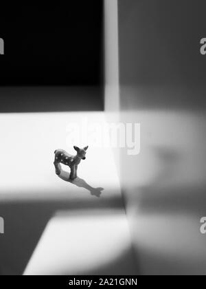 Surreal image of a toy fawn in the black and white background - Stock Photo