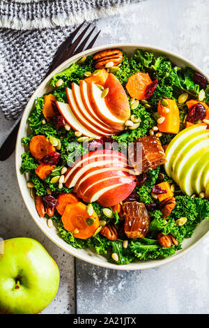 Winter salad with apple, pumpkin, cranberries, honey and seeds in a white plate. Healthy vegan food concept. - Stock Photo