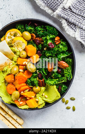 Avocado hummus with baked vegetables, olives, nuts and berries in a black plate. Healthy vegan food concept. - Stock Photo