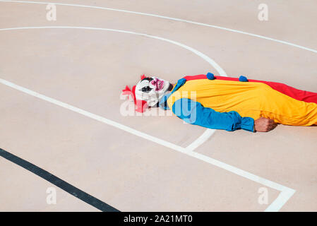 a scary clown, wearing a colorful yellow, red and blue costume, lying face up on an outdoor basketball court - Stock Photo