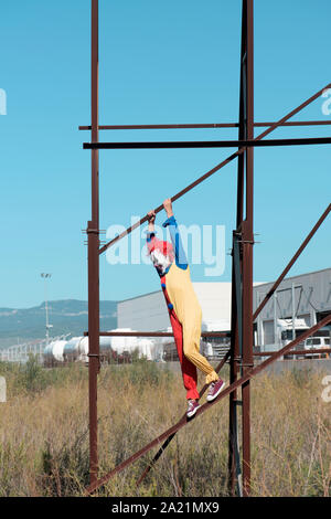 a scary clown wearing a colorful yellow, red and blue costume outdoors, hanging from the rusty structure of an abandoned billboard - Stock Photo