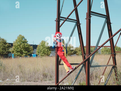 a scary clown wearing a colorful yellow, red and blue costume outdoors, stacking out his tongue and doing the sign of the horns while hanging from the - Stock Photo