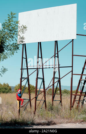 a scary clown wearing a colorful yellow, red and blue costume outdoors, hanging from the rusty structure of an abandoned billboard with no ads - Stock Photo