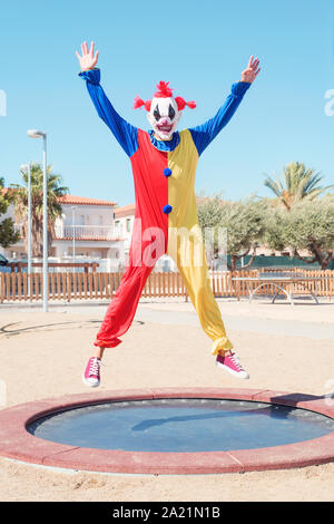a scary clown wearing a colorful yellow, red and blue costume bouncing on a trampoline in an outdoor public playground - Stock Photo