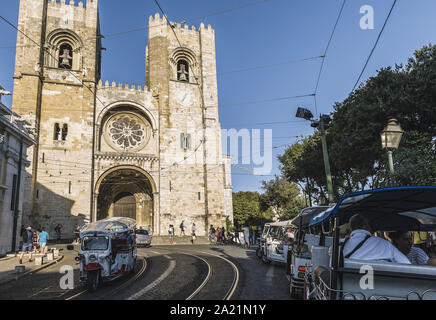 Lisbon, Portugal – august, 2019: touristic tuktuk passing by the cobblestone street in front of the cathedral at Alfama district - Stock Photo
