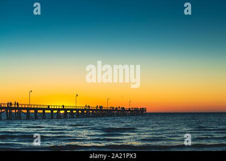 Semaphore Beach jetty with people enjoying spectacular sunset, South Australia - Stock Photo