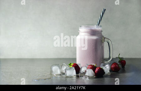 Strawberry milkshake, pink protein drink with strawberry and ice on a gray background. Copy space, place for text. - Stock Photo