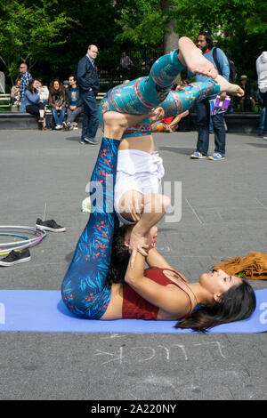 Two young ladies do acroyoga exercises in front of a crowd near the fountain in Washington Square Park, New York City. - Stock Photo