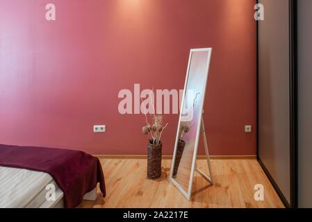Bedroom in scarlet tones. Laminate floor. Vase with decorative flowers. - Stock Photo