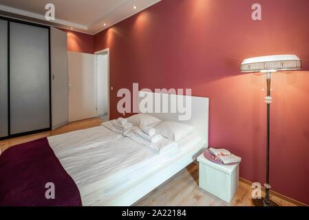 Modern bedroom in scarlet tones. Floor lamp. Wardrobe. - Stock Photo