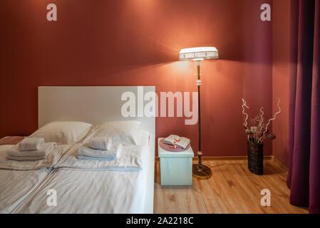 Modern bedroom in scarlet tones. Floor lamp. Bedside. - Stock Photo