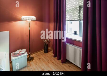 Modern bedroom in scarlet tones. Window with curtains. Floor lamp. - Stock Photo
