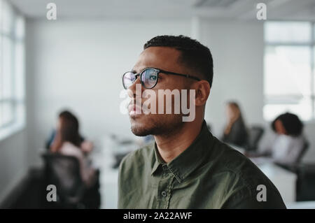 Close-up of a young african american business man entrepreneur wearing eyeglasses contemplating in office