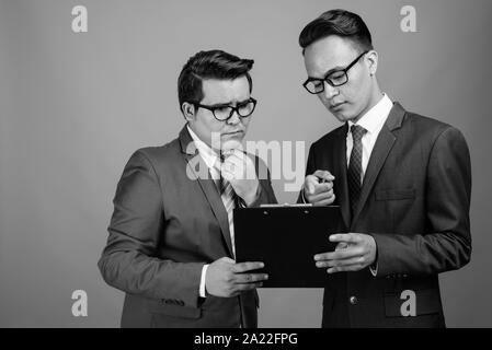 Young multi-ethnic businessman and young Indian businessman against gray background - Stock Photo