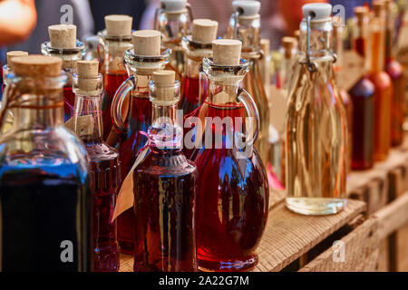 Bottles of homemade liqueur and schnapps on a wooden shelf - Stock Photo