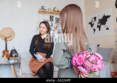 Little girl giving her mother bouquet of pink peonies - Stock Photo