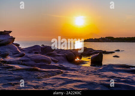 Silhouette of Holy Mount Athos, Greece at colorful sunrise or sunset, rocks and sea panorama from Karidi beach, Vourvourou, Sithonia - Stock Photo