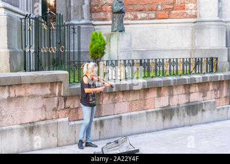 Oviedo, Spain - 30.09.2019 Girl street musician plays the violin on the street near the fence of the ancient church. Art in the city - Stock Photo