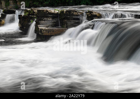 Long exposure with blurred water of River Swale Waterfalls in Richmond North Yorkshire England - Stock Photo