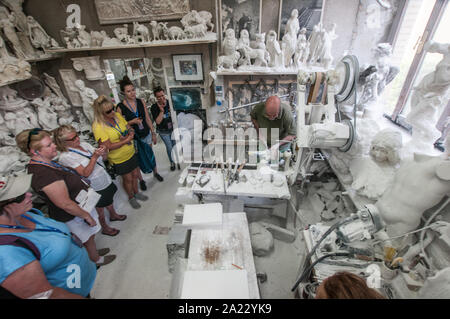 The artisan Roberto Chiti specializes in alabaster, working in his own workshop demonstrating to tourists - Stock Photo