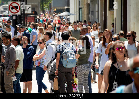 people waiting to cross street on busy crowded sidewalk on michigan avenue downtown chicago illinois united states of america - Stock Photo