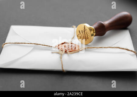 Notary public wax stamper. White envelope with brown wax seal, golden stamp. Responsive design mockup, flat lay. Still life with postal accessories - Stock Photo