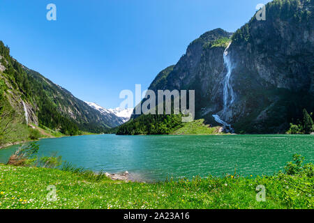 Mountain landscape with clear turquoise lake and waterfall in the Alps. Zillertal Alps Nature Park, Austria, Tyrol. - Stock Photo