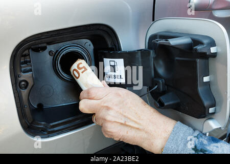 Hand of a woman putting euros banknotes in a car tank - Stock Photo