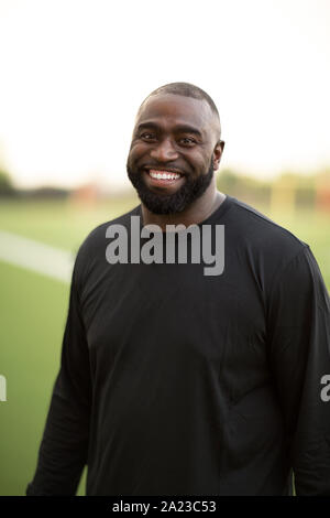 Portrait of an African American Football coach smiling. - Stock Photo