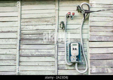 Modern electrical meter hanging on the old wooden house in the village outdoors - Stock Photo