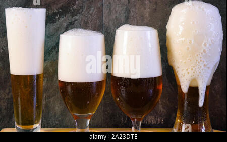 Pouring beer into traditional beer glasses on black slate bar table, beer tasting on wooden paddle. - Stock Photo